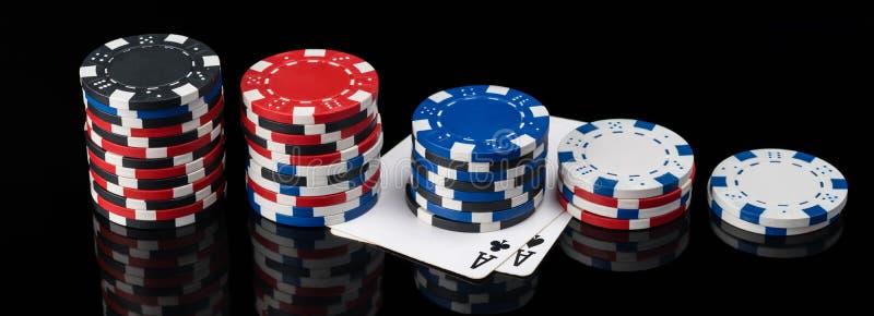 As microplaquetas e os cartões do pôquer encontram-se de comprimento em um fundo preto com imagem de stock royalty free