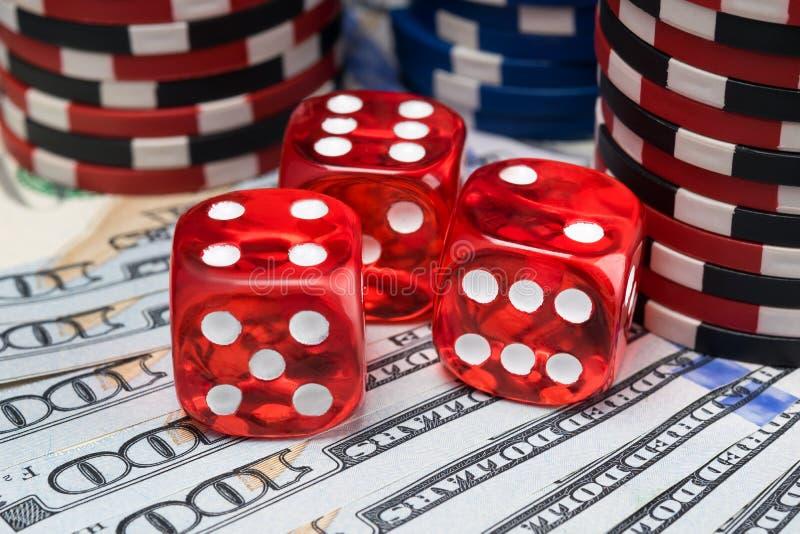 As microplaquetas vermelhas dos dados e de pôquer estão no fundo do dinheiro imagem de stock