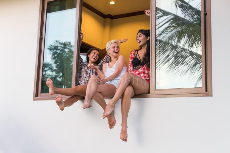 As moças agrupam o assento no peitoril da janela que falam, uma comunicação bonita dos amigos da mulher imagens de stock royalty free
