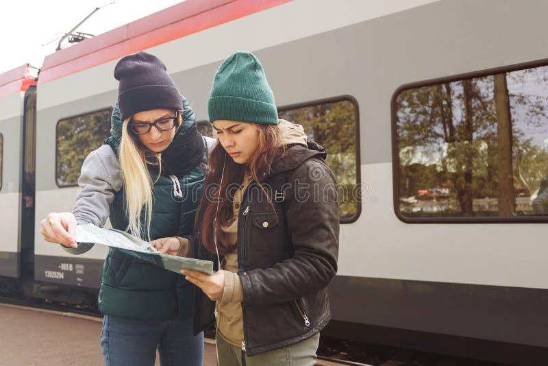 As moças do moderno com trouxa e mapa esperam o trem Mulheres que viajam apenas no estação de caminhos-de-ferro, conceito do curs fotos de stock