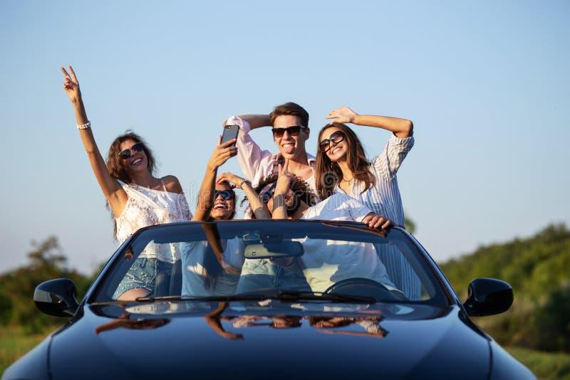 As moças e os indivíduos engraçados nos óculos de sol estão sentando-se em um cabriolet preto na estrada que mantém suas mãos e f fotografia de stock royalty free