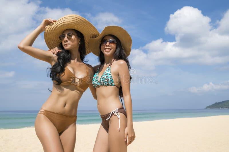 As moças 'sexy' asiáticas no biquini, apreciam vestir o chapéu de palha e os sunglass, andando na praia, curso de férias de verão imagem de stock