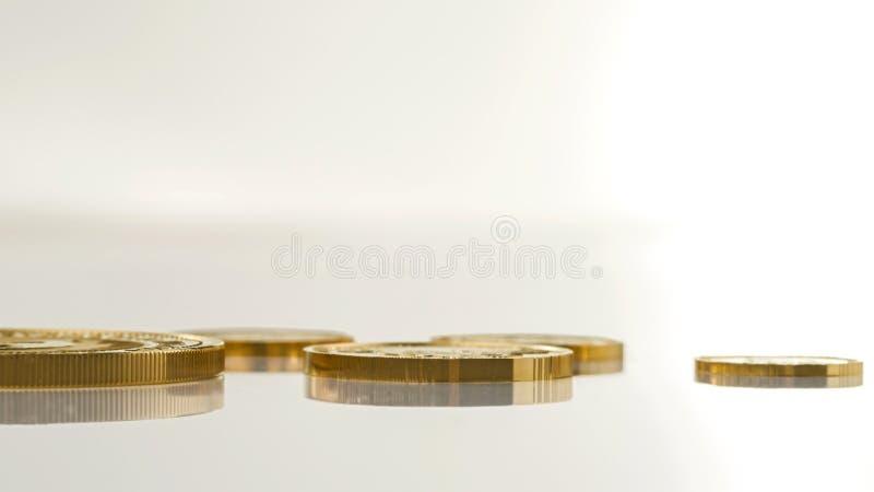 As moedas de ouro de tamanhos diferentes encontram-se em uma superfície da luz imagens de stock royalty free