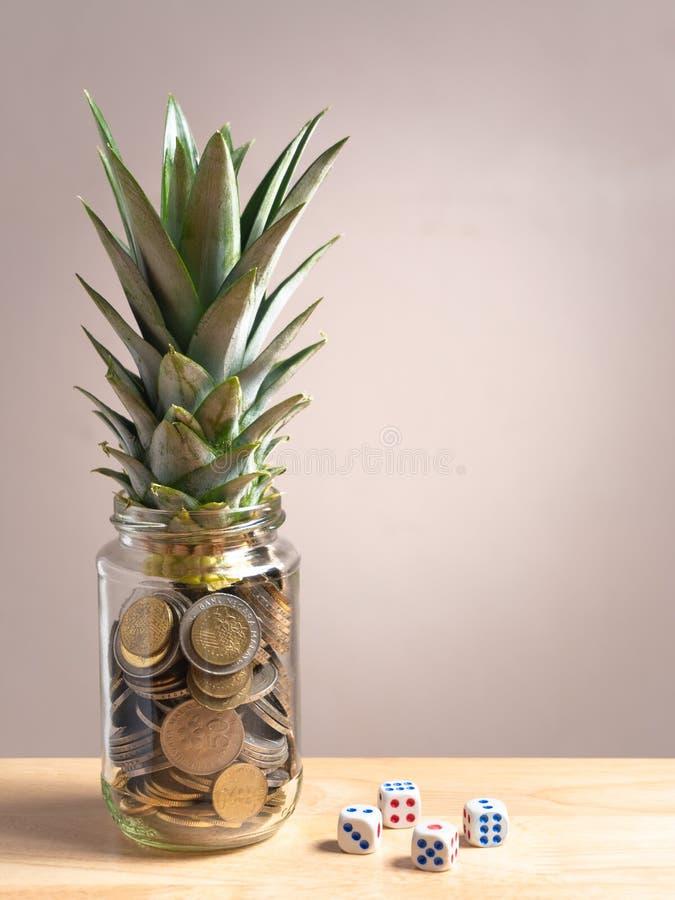 as moedas de um centavo na garrafa de vidro com abacaxi folheiam na parte superior e cortam no outro lado fotos de stock