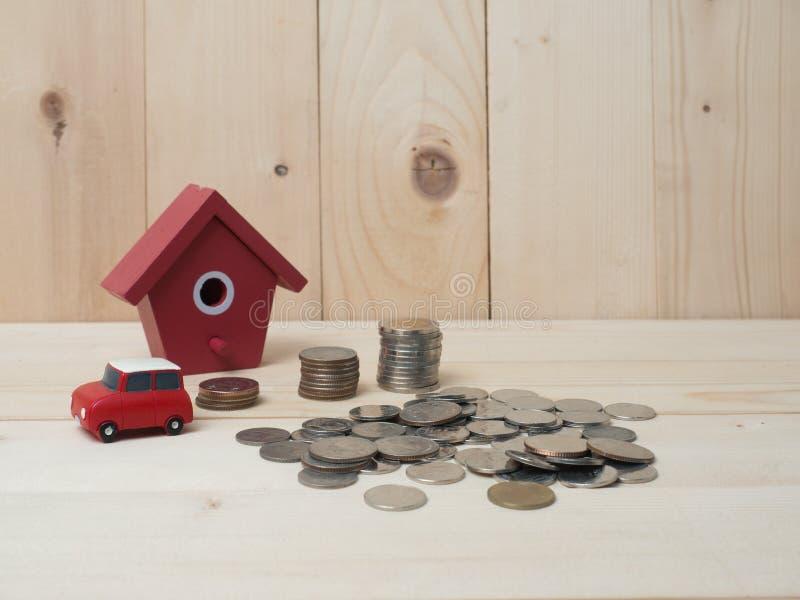 As moedas do dinheiro empilham o crescimento com a casa vermelha no fundo de madeira foto de stock