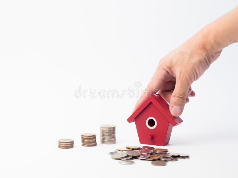 As moedas do dinheiro empilham o crescimento com a casa vermelha no fundo de madeira fotografia de stock