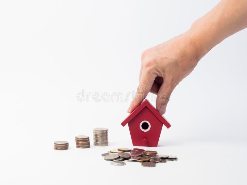 As moedas do dinheiro empilham o crescimento com a casa vermelha no fundo de madeira imagem de stock royalty free