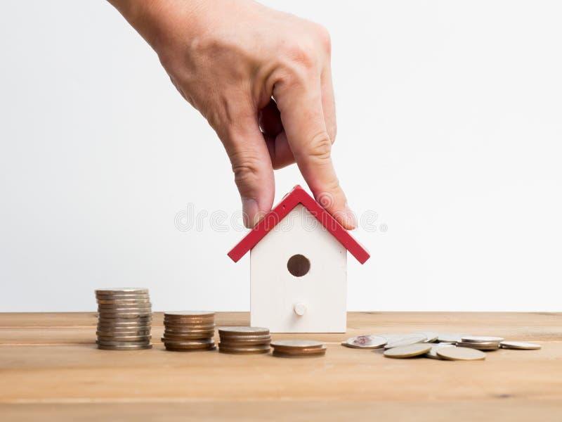 As moedas do dinheiro empilham o crescimento com a casa vermelha no fundo de madeira Investimento do crescimento do negócio e ide fotos de stock royalty free