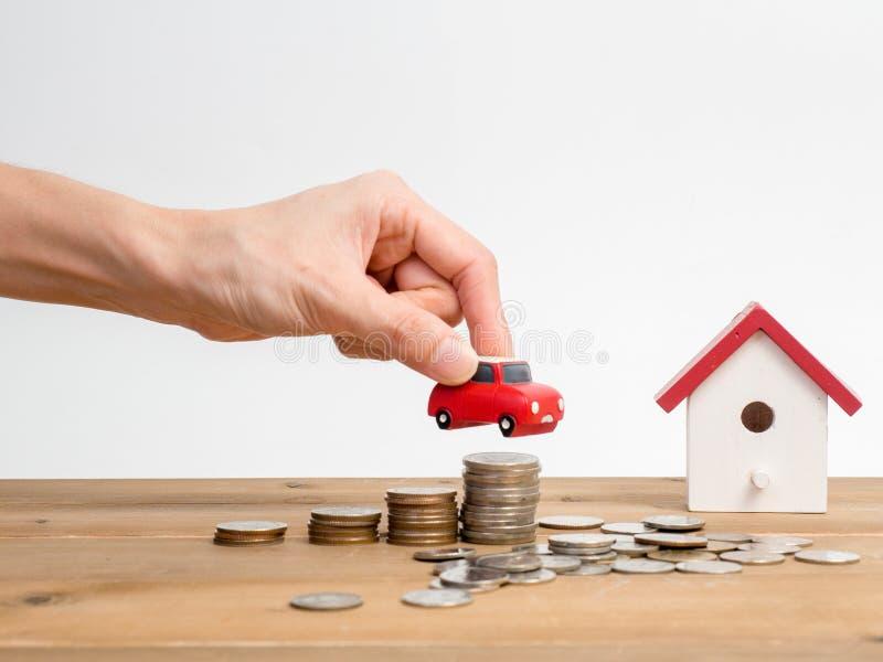 As moedas do dinheiro empilham o crescimento com a casa vermelha no fundo de madeira Investimento do crescimento do negócio e ide imagens de stock royalty free