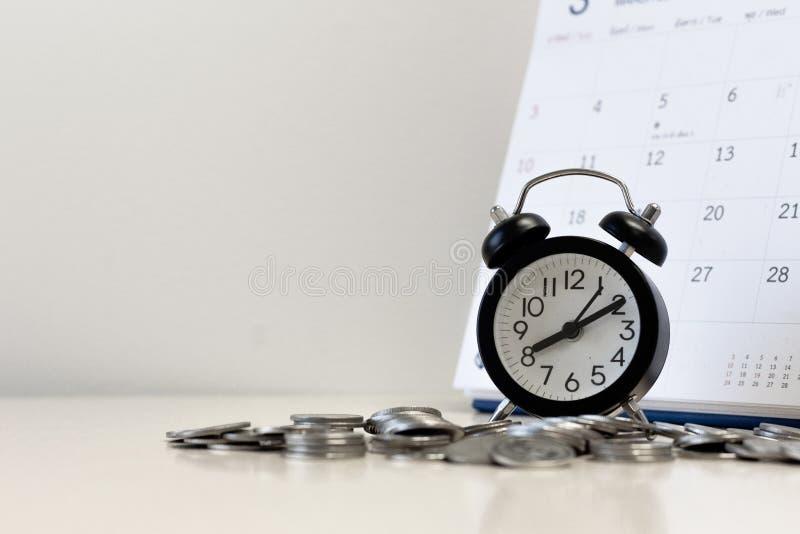 As moedas do dinheiro pisam com calendário e despertador, tempo do imposto e conceito de salvamento do dinheiro e o financeiro pl imagens de stock royalty free