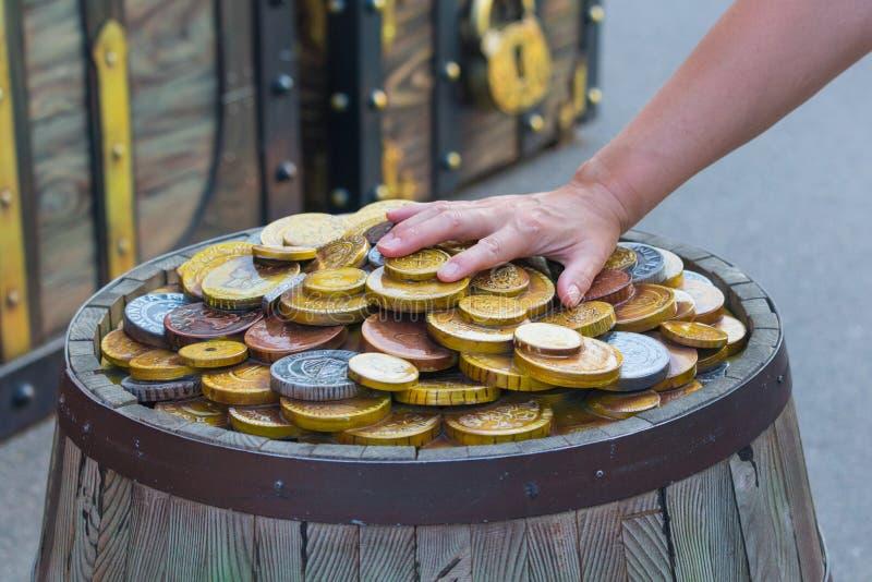 As moedas encontram-se em um dinheiro que de madeira de Rast do tambor o homem fabuloso da riqueza mantém sua mão fazer um lucro  fotos de stock royalty free
