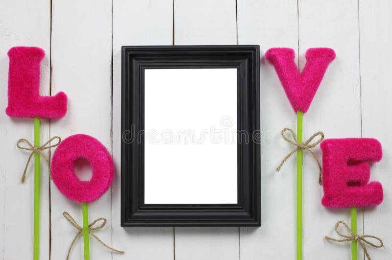 As molduras para retrato e as letras vermelhas do amor são colocadas imagem de stock royalty free