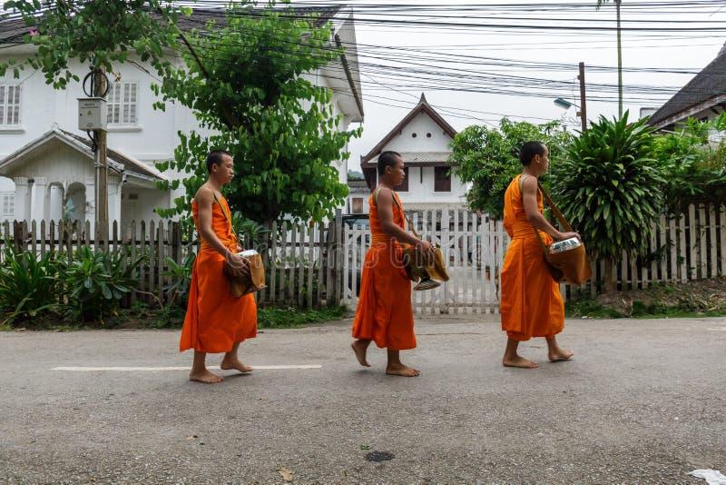 As monges budistas do principiante recolhem a esmola em Luang Prabang, Laos foto de stock