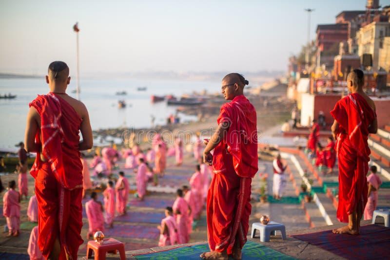 As monges hindu novas conduzem uma cerimônia para encontrar o alvorecer em bancos de Ganges, e aumentam a bandeira indiana imagem de stock