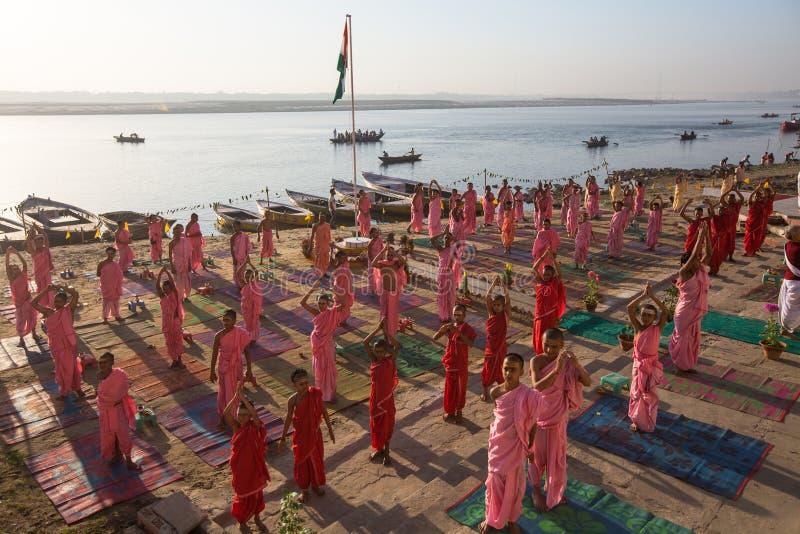 As monges hindu novas conduzem uma cerimônia para encontrar o alvorecer em bancos de Ganges, e aumentam a bandeira indiana imagens de stock royalty free