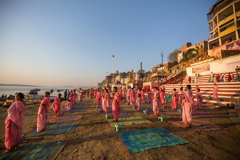 As monges hindu novas conduzem uma cerimônia para encontrar o alvorecer nos bancos do Ganges, e aumentam a bandeira indiana foto de stock