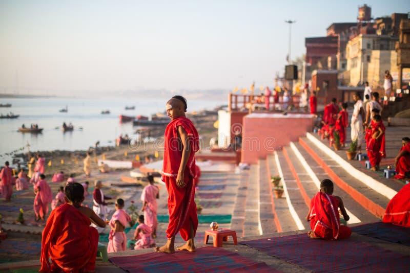As monges hindu novas conduzem uma cerimônia para encontrar o alvorecer nos bancos do Ganges, e aumentam a bandeira indiana fotografia de stock