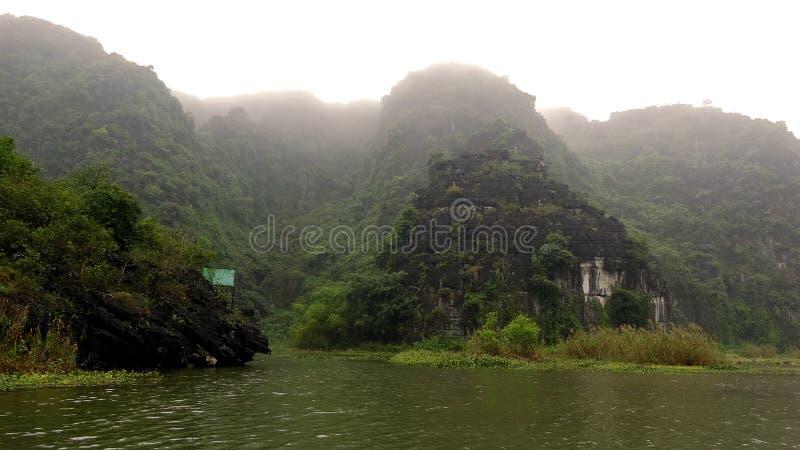 As montanhas da pedra calcária esticam-se fora da água foto de stock royalty free