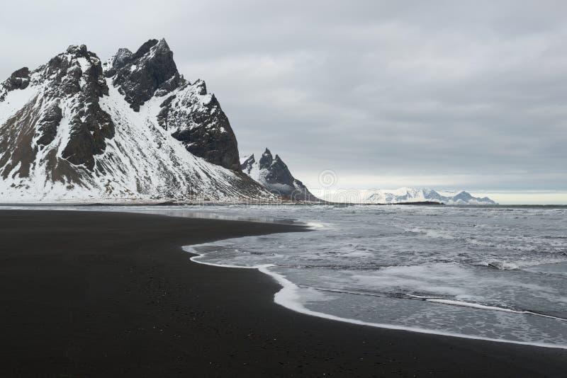 As montanhas da península, do Vestrahorn de Stokksnes e o oceano preto da areia costeiam a linha, Islândia foto de stock