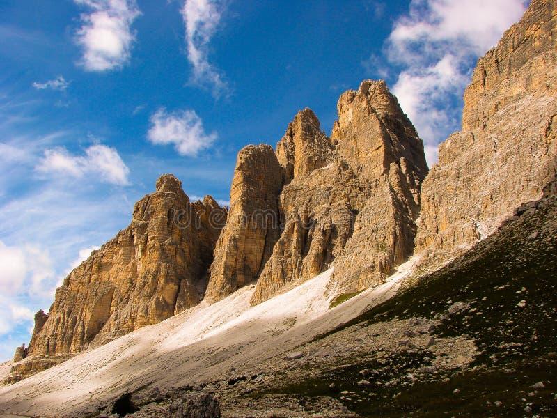 As montanhas das dolomites nublam-se o penhasco das rochas do céu azul dos picos de Italia dos penhascos da escalada do lavaredo  fotos de stock