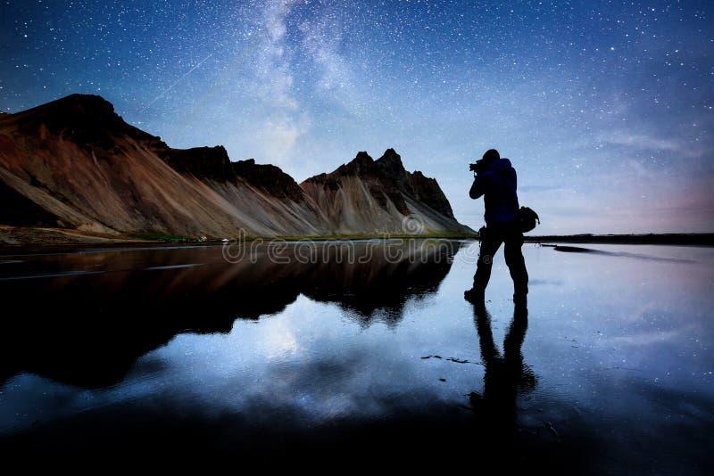 As montanhas de surpresa refletiram na água na noite estrelado Stoksnes, Islândia Silhueta do fotógrafo da natureza dentro imagem de stock royalty free
