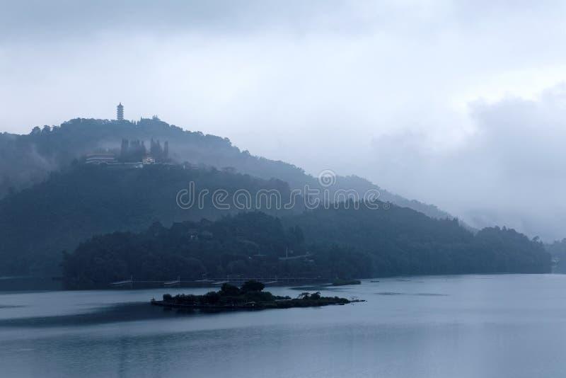 As montanhas enevoadas em Sun Moon o lago em uma manhã nevoenta, com um pagode no cume distante sob o céu nebuloso temperamental imagem de stock royalty free