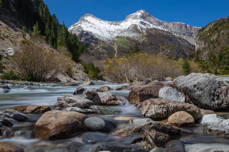 As montanhas nevados & as rochas do rio fotografia de stock royalty free