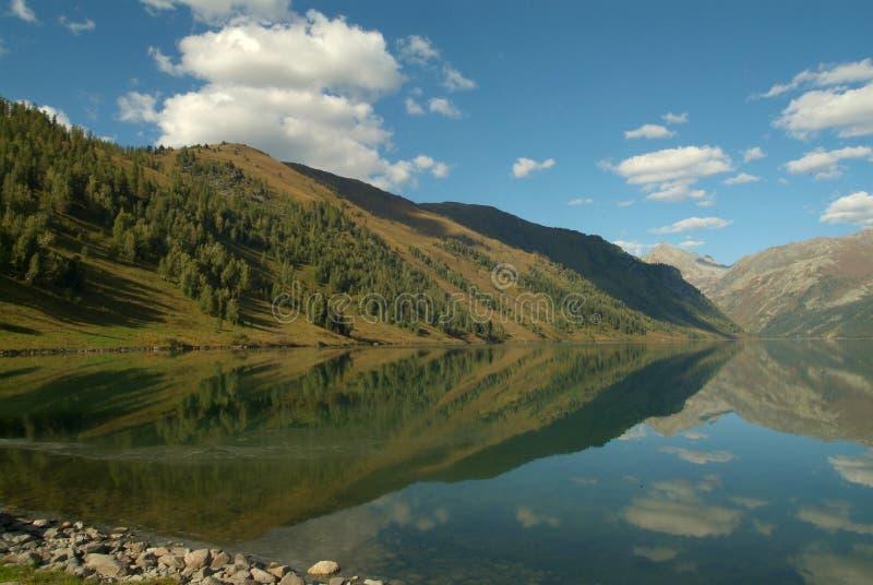 As montanhas simétricas refletiram no lago com um céu azul bonito e umas nuvens macias fotografia de stock royalty free