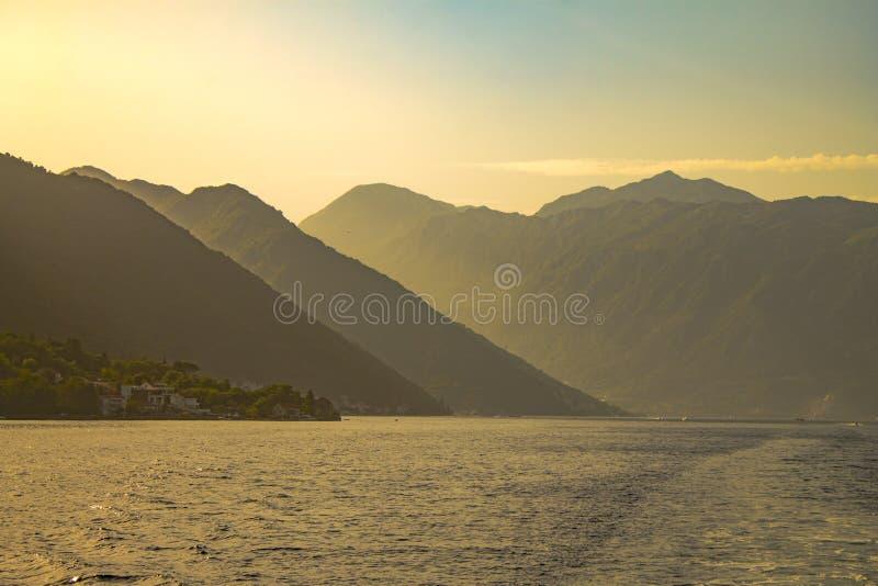 As montanhas surpreendentes e a paisagem ensolarada da água com névoa latem em Kotor, Montenegro fotos de stock