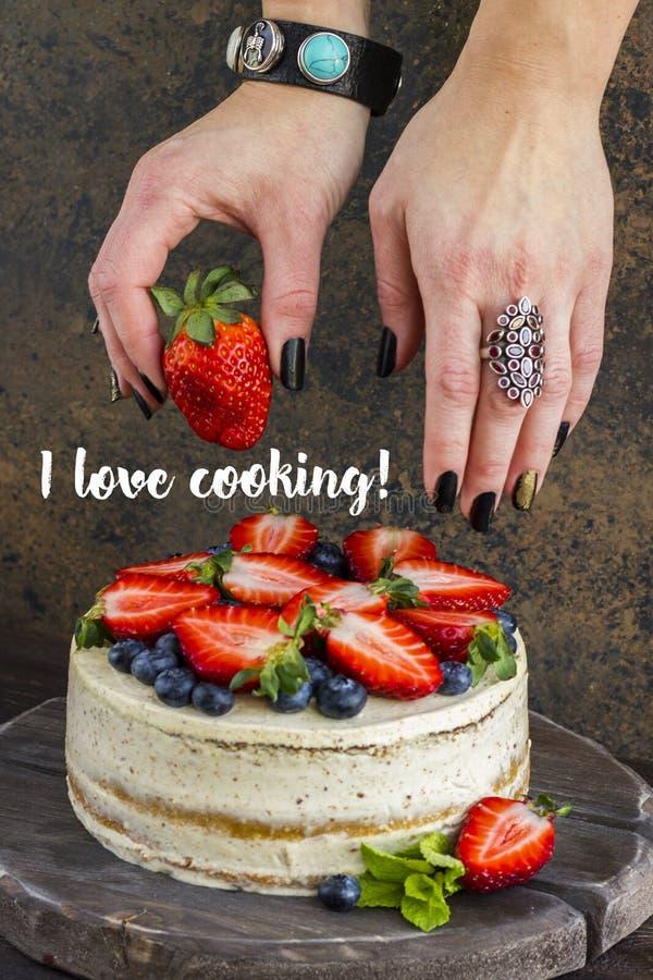 As morangos em uma mão do ` s da mulher decoram um bolo com bagas fotografia de stock