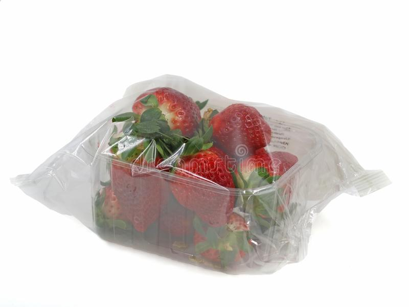 As morangos frescas envolveram com folha no recipiente plástico imagens de stock royalty free