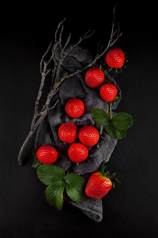 As morangos maduras frescas em um guardanapo e em uma ardósia chapeiam a mesa de cozinha fotografia de stock royalty free