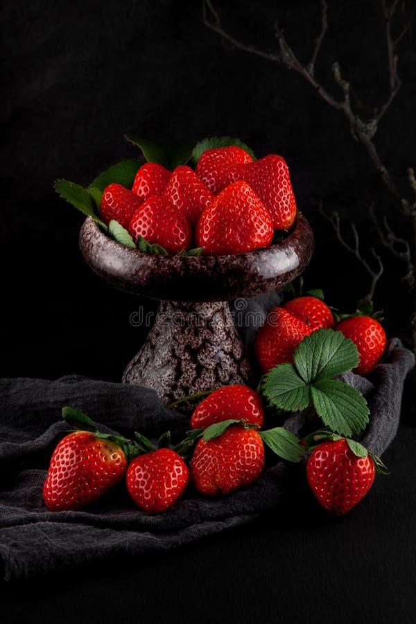 As morangos maduras frescas em um guardanapo e em uma ardósia chapeiam a mesa de cozinha fotos de stock royalty free