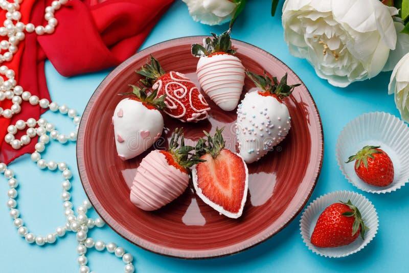 As morangos maduras no esmalte branco do chocolate colocam em uma placa perto das flores brancas e dos grânulos da pérola em um f fotografia de stock