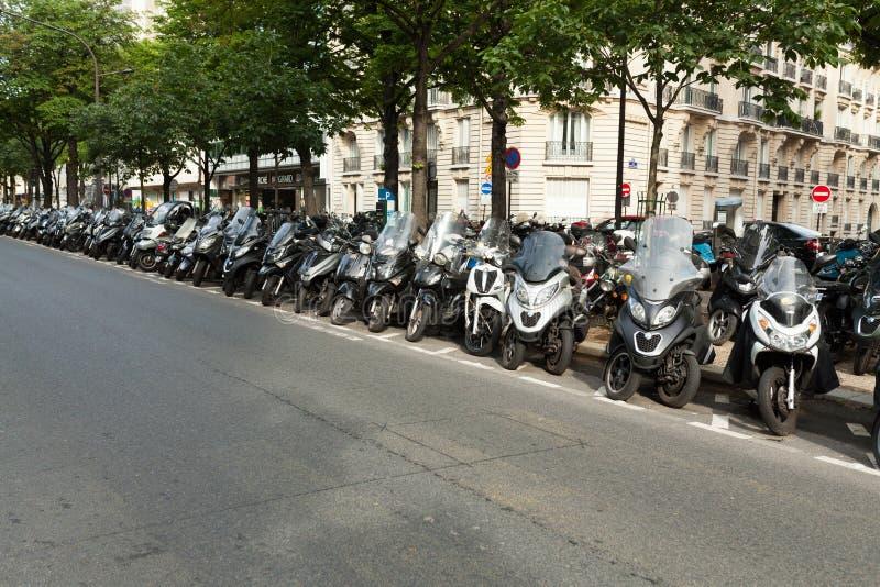 As motocicletas e as bicicletas motorizadas no estacionamento da rua em um dia de verão ensolarado em Paris França podem 2018 imagem de stock