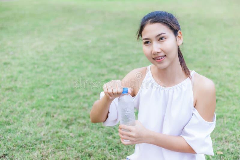 As mulheres abrem a garrafa no parque após o exercício foto de stock