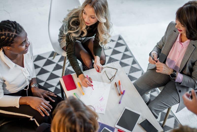 As mulheres africanas e caucasianos encontram-se no estúdio, após a sessão de formação do sofá foto de stock