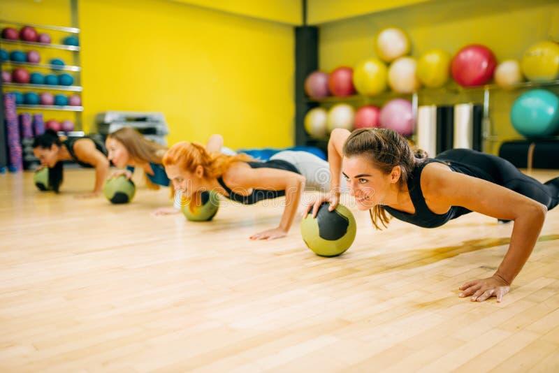 As mulheres agrupam com bolas que fazer levanta o exercício imagens de stock