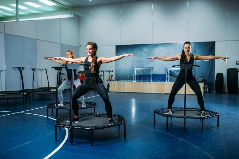 As mulheres agrupam fazer o exercício apto no trampolim do esporte fotos de stock royalty free