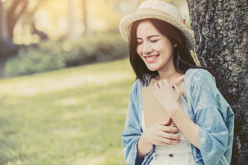 As mulheres asiáticas abraçam o livro e os desaparecidos do diário uma boa memória passada fotografia de stock