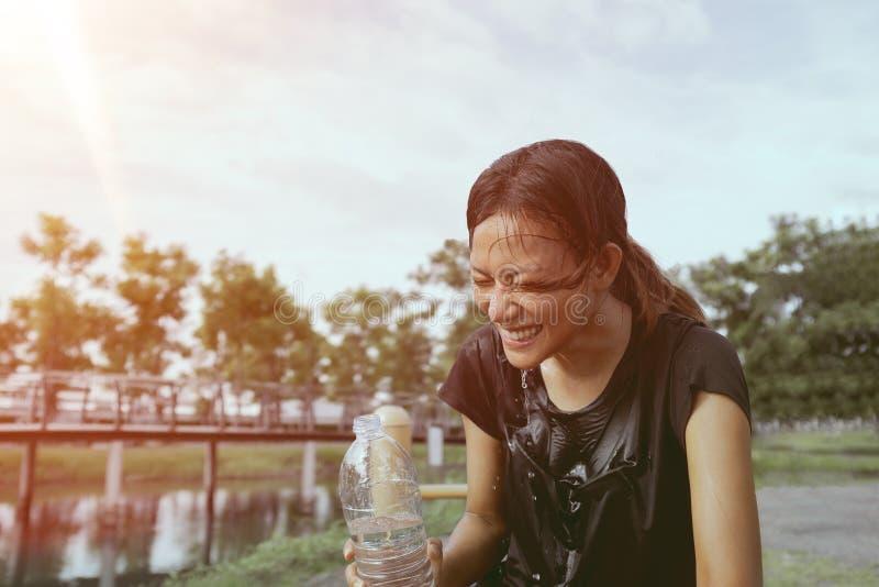 As mulheres asiáticas estão espirrando a água a sua cara para relaxar imagem de stock
