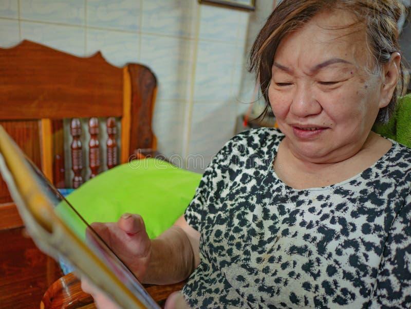 As mulheres asiáticas idosas muito felizes olham a tabuleta em sua casa fotos de stock royalty free