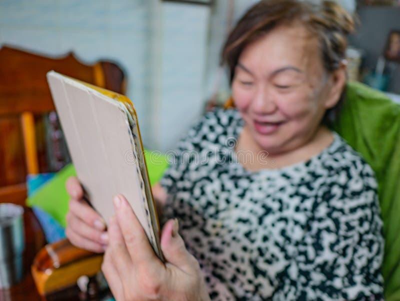 As mulheres asiáticas idosas muito felizes olham a tabuleta em sua casa, c velho fotografia de stock