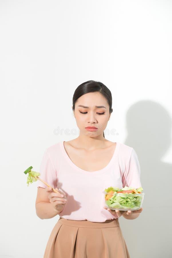 As mulheres asiáticas infelizes estão no tempo de dieta a menina não quer comer vegetais e não gostar do gosto do vegetal fotografia de stock