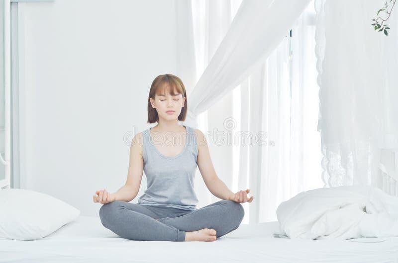 As mulheres asiáticas jogam a ioga na cama na sala de manhã fotos de stock royalty free