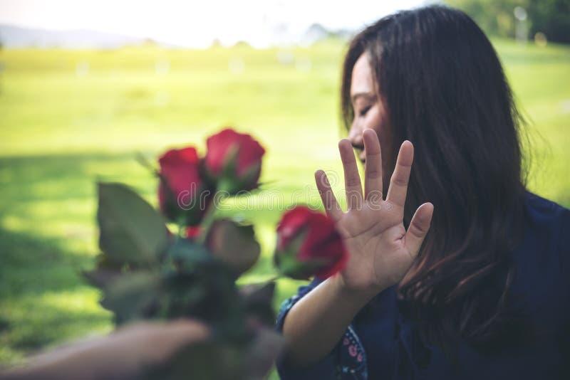 As mulheres asiáticas que rejeitam uma rosa vermelha florescem de seu noivo no dia do ` s do Valentim foto de stock royalty free