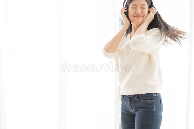 As mulheres asiáticas relaxam escutando a música usando fones de ouvido e dançando imagens de stock