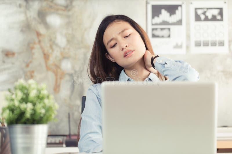 As mulheres asiáticas têm a dor de pescoço do trabalho no escritório imagem de stock royalty free
