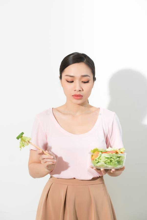 As mulheres asi?ticas infelizes est?o no tempo de dieta a menina n?o quer comer vegetais e n?o gostar do gosto do vegetal imagens de stock