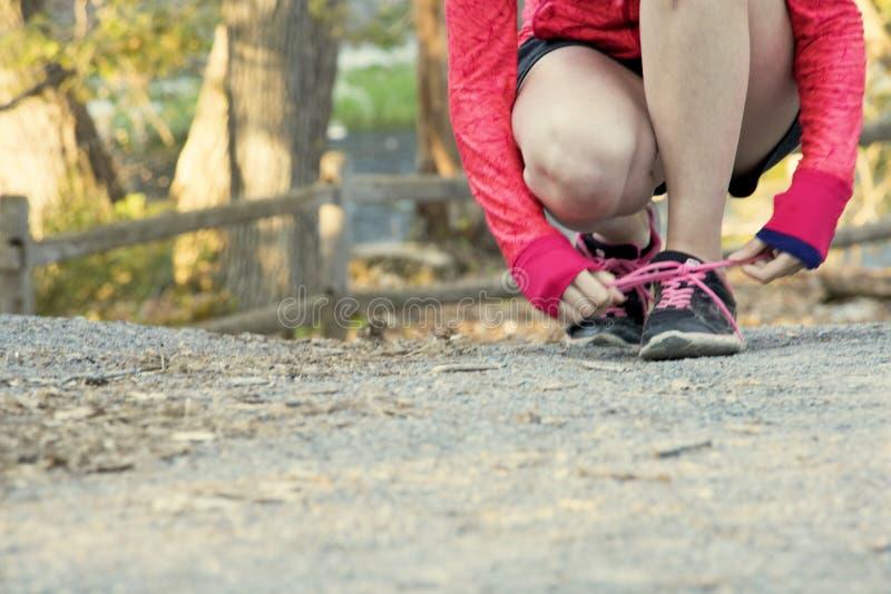 As mulheres atléticas aptas dobraram-se para baixo ao laço da mostra do laço em uma fuga exterior imagens de stock